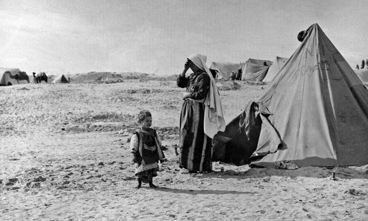 في غزة، خان يونس، تقف هذه الفلسطينية وطفلها خارج خيمة المخيم 1948