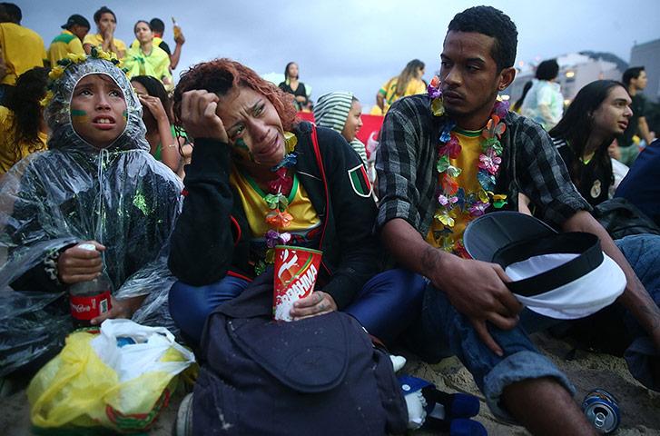 حزن الجماهير التي تابعت اللقاء من شاطيء كوباكابانا الشهير في ريو دي جانيرو - Photograph: Mario Tama/Getty Images