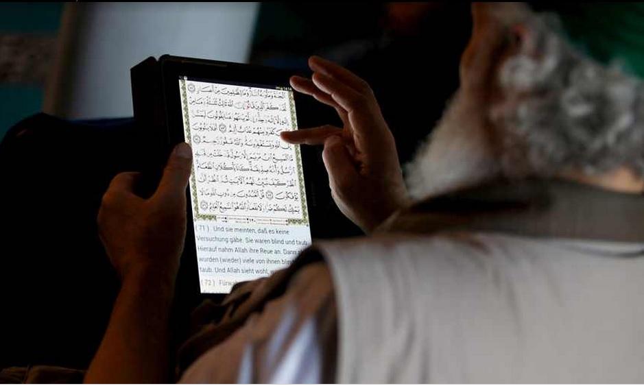 في برلين يقرأ القر'آن من جهازه بالعربية والألمانية