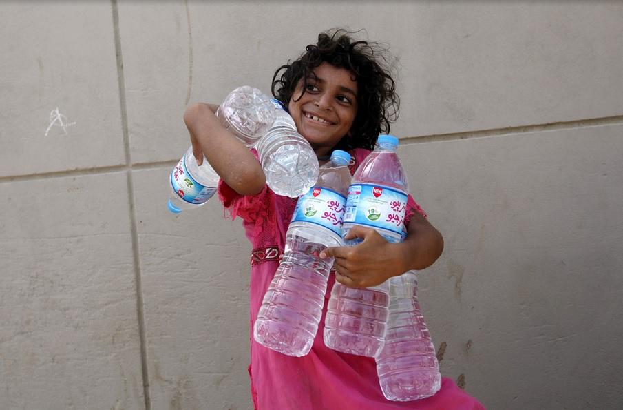 طفلة تبتسم لنجاحها في جمع عدد من زجاجات المياه  من نقطة توزيع خيرية في كراتشي، باكستان