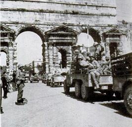 خارج البورتا ماجوري، أحد المداخل الرئيسية لروما، تلوح يد الرقيب جيمي ديكلاي مؤذنة بدخول الجيش الأمريكي إلى المدينة الخالدة