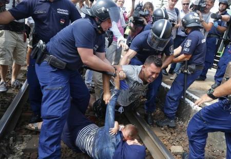 أفراد أمن مجريون يعتقلون مهاجرين يرقدون على قضبان للسكك الحديدية في محطة ببلدة بيتشكه المجرية يوم الخميس. تصوير: لازلو بالوج - رويترز