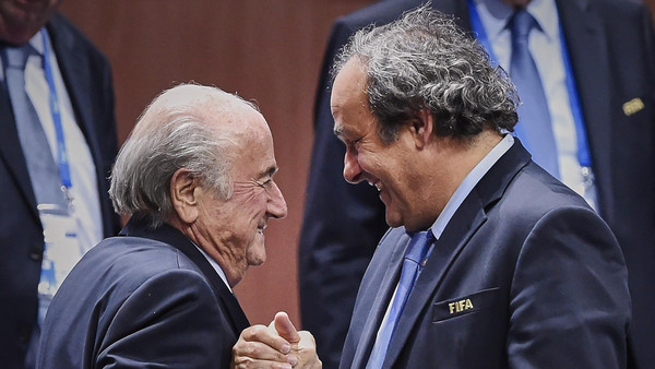 "(FILES)-- A file photo taken on May 29, 2015 shows FIFA President Sepp Blatter (L) shaking hands with UEFA President Michel Platini after being re-elected following a vote to decide on the FIFA presidency in Zurich. UEFA chief Michel Platini revealed in a letter sent on September 28, 2015 to 54 European UEFA federations, that a payment made to him from Blatter had been ""fully declared"" to authorities. AFP PHOTO / MICHAEL BUHOLZER"