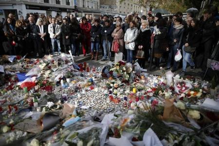 أشخاص يقفون دقيقة صمت حدادا على أرواح ضحايا هجمات باريس يوم الاثنين. تصوير: كريستيان هارتمان - رويترز.