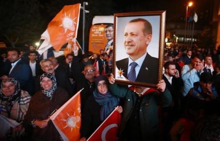 أناس يرفعون صورة لاردوغان خارج مقر حزب العدالة والتنمية في اسطنبول يوم الأحد. تصوير. عثمان أورسال - رويترز