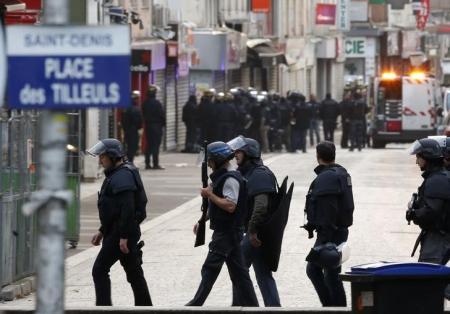 قوات الشرطة الفرنسية الخاصة تؤمن المنطقة المحيطة أثناء تبادل لإطلاق النار في ضاحية سان دوني في باريس يوم الأربعاء. تصوير: جاكي نايجلن - رويترز