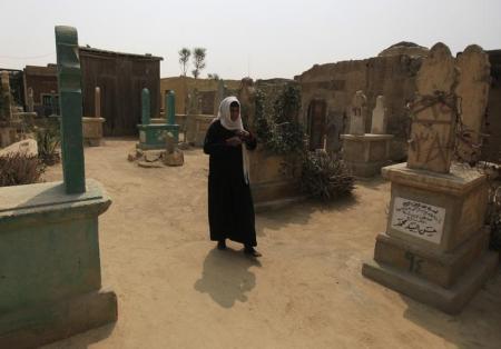 صورة من أرشيف رويترز لامرأة تسير وسط المقابر في القاهرة.
