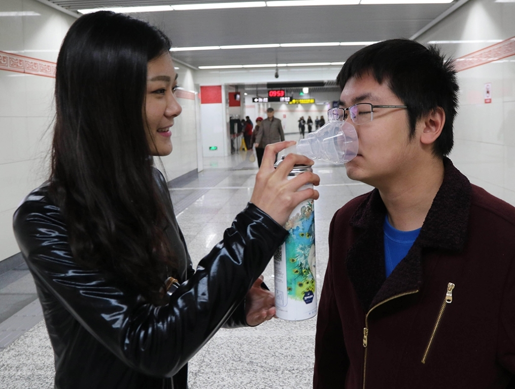 F635YX A man breathes in the canned fresh air at a subway station during a promotional event of a real estate developer in Zhengzhou in central China's Henan province Tuesday Nov. 10, 2015.