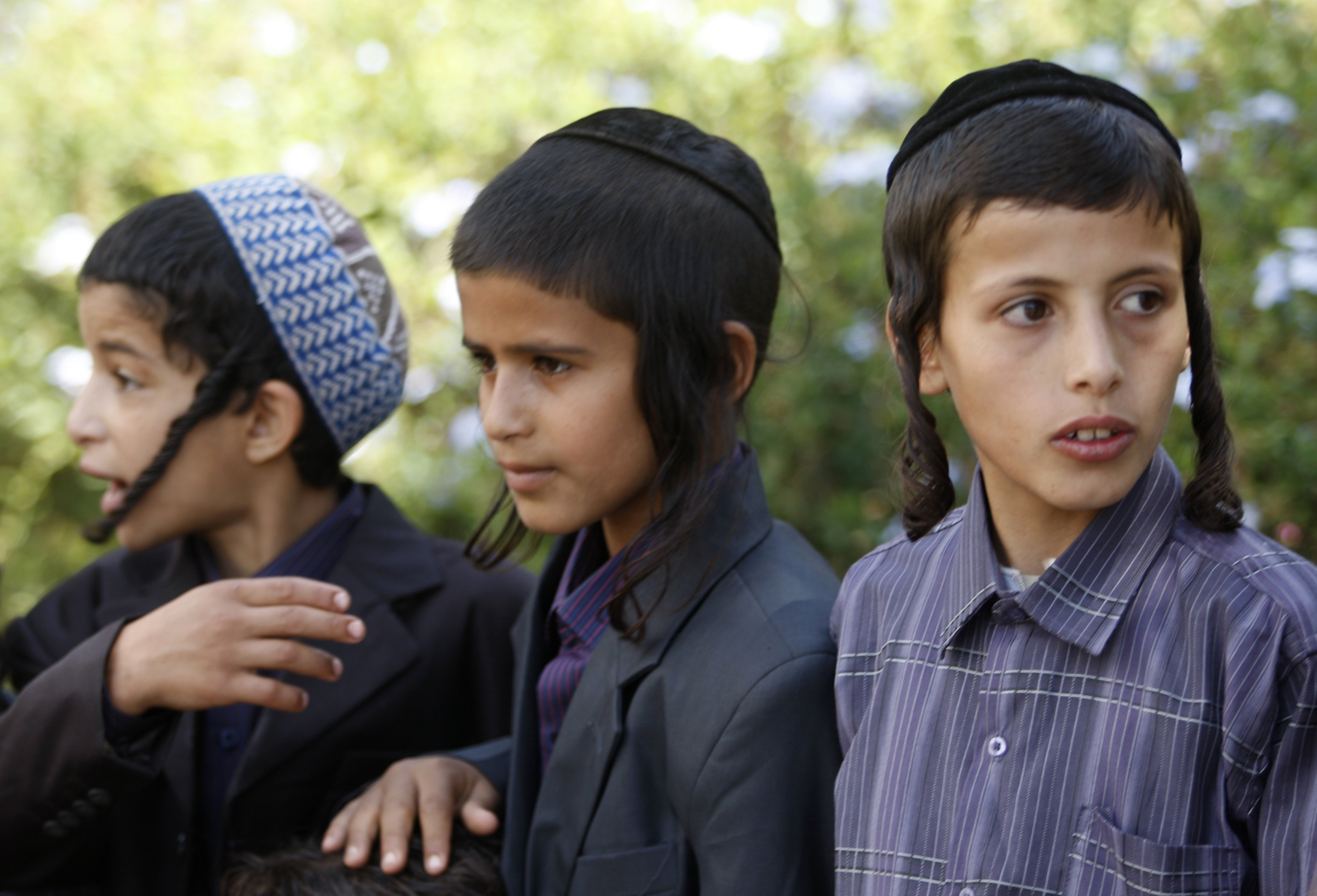 "Yemeni Jewish boys are seen at their housing compound during the Jewish Passover holiday in Sanaa in this April 9, 2009 file photo. A few worried families are all that remain of Yemen's ancient Jewish community, and they too may soon flee after a Shi'ite Muslim militia seized power in the strife-torn country this month. Harassment by the Houthi movement - whose motto is ""Death to America, death to Israel, curse the Jews, victory to Islam"" - caused Jews in recent years to largely quit the northern highlands they shared with Yemen's Shi'ites for millennia. But political feuds in which the Jews played no part escalated last September into an armed Houthi plunge into the capital Sanaa, the community's main refuge from which some now contemplate a final exodus.  REUTERS/Khaled Abdullah/Files (YEMEN - Tags: RELIGION POLITICS CIVIL UNREST)"