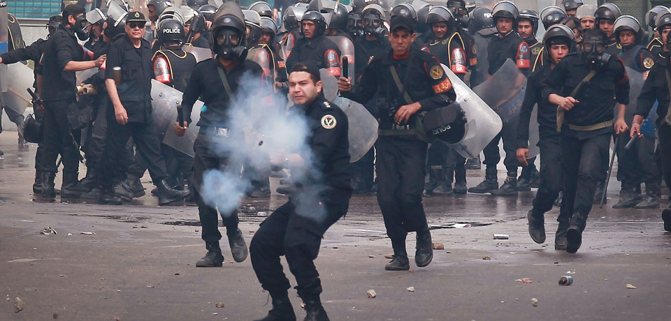 CAIRO, EGYPT - JANUARY 28:  A riot policeman fires tear gas at protestors in front of the l-Istiqama Mosque in Giza on January 28, 2011 in Cairo, Egypt. Thousands of police are on the streets of the capital and hundreds of arrests have been made in an attempt to quell anti-government demonstrations.  (Photo by Peter Macdiarmid/Getty Images)