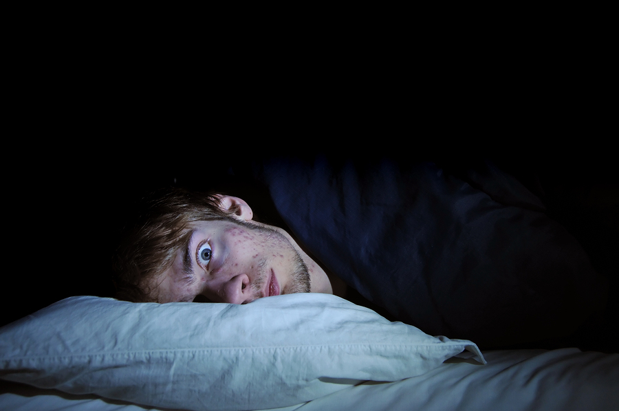 White male caucasian young adult on bed with head on pillow with eyes wide open staring off into space at the camera. Afraid of the dark.