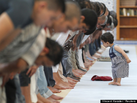 A child walks near members of the Muslim community attending midday prayers at Strasbourg Grand Mosque in Strasbourg on the first day of Ramadan July 9, 2013. The Grand Mosque of Paris has fixed the first day of Ramadan as Wednesday, splitting with the French Council of Muslim Religion (Conseil Francais du Culte Musulman or CFCM), which determined it would begin on Tuesday.  REUTERS/Vincent Kessler (FRANCE - Tags: RELIGION TPX IMAGES OF THE DAY) - RTX11HMH