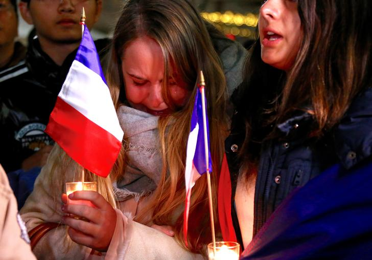 Members of the Australian French community cry as they sing the French national anthem during a vigil in central Sydney, Australia, July 15, 2016 to remember the victims of the Bastille Day truck attack in Nice. REUTERS/David Gray TPX IMAGES OF THE DAY