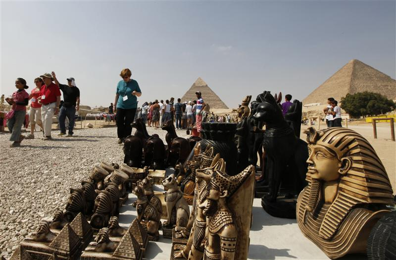 Souvenirs are seen as tourists visit the Pyramids of Giza in Cairo October 19, 2011. Tourist numbers have plummeted, dealing a blow to the millions of Egyptians whose livelihoods depend on the 14 million or more visitors who once came to Egypt annually, providing one in eight jobs in a country beset by high unemployment.   REUTERS/Jamal Saidi (EGYPT - Tags: SOCIETY TRAVEL BUSINESS)