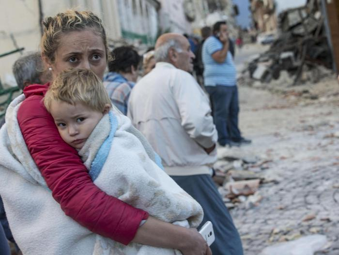 A mother embraces his son in Amatrice, central Italy, where a 6.1 earthquake struck just after 3:30 a.m.,Italy, 24 August 2016. The quake was felt across a broad section of central Italy, including the capital Rome where people in homes in the historic center felt a long swaying followed by aftershocks. ANSA/ MASSIMO PERCOSSI