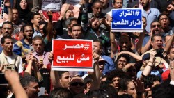 "Egyptian protesters with placards shout slogans during a demonstration against a controversial deal to hand two islands in the Red Sea to Saudi Arabia on April 15, 2016 outside the Journalists' Syndicate in central Cairo. The placards read in Arabic: ""Egypt is not for sale"" (L) and ""the decision are the people's decisions"" (R). Outside the Journalists' Syndicate in central Cairo, about 200 protesters chanted ""down with military rule"", the signature slogan of the 2011 Arab Spring uprisings. The deal to hand over two islands in the Straits of Tiran, signed during a visit by Saudi Arabia's King Salman to Cairo last week, has provoked a storm of criticism against Egyptian President Abdel Fattah al-Sisi.   / AFP / MOHAMED EL-SHAHED        (Photo credit should read MOHAMED EL-SHAHED/AFP/Getty Images)"