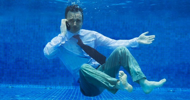 Businessman Using Cell Phone Underwater --- Image by © Paul Hardy/Corbis