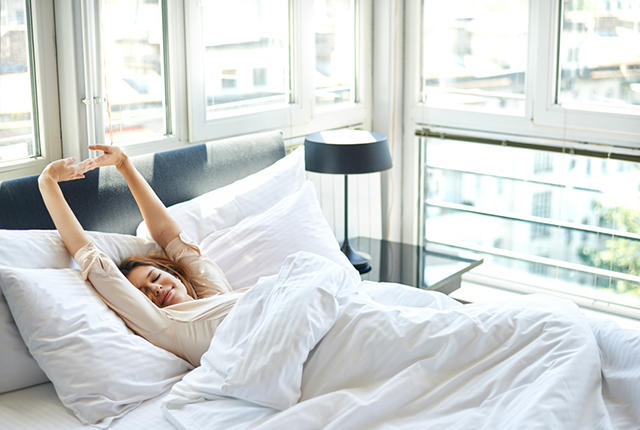 Young woman is doing morning stretching in bed, arms raised, rear view