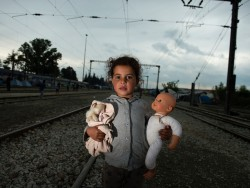 A young girl holding dolls poses on the railroad tracks near a makeshift camp for migrants and refugees near the village of Idomeni, not far from the Greek-Macedonian border, on May 2, 2016.  Some 54,000 people, many of them fleeing the war in Syria, have been stranded on Greek territory since the closure of the migrant route through the Balkans in February. More than 10,000 are in the overcrowded camp in Idomeni, separated from Macedonia with a double barbed wire fence. / AFP / TOBIAS SCHWARZ        (Photo credit should read TOBIAS SCHWARZ/AFP/Getty Images)
