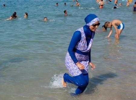 سيدة ترتدي البوركيني تسير في المياه على شاطئ في مرسيليا يوم 27 أغسطس آب 2016. تصوير: رويترز.