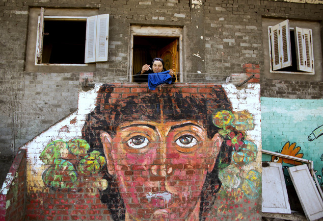 In this Thursday, Oct. 13, 2016 photo, an Egyptian woman hangs her laundry over a mural by Egyptian artist Omar El Fayoumi in Burullus, north of Cairo, Egypt. For the third successive year, the Egyptian fishing town of Burullus has played host to a unique art festival that attracts participants from home and abroad, injecting life and color into the town, its walls and the estimated 100,000 residents.(AP Photo/Amr Nabil)