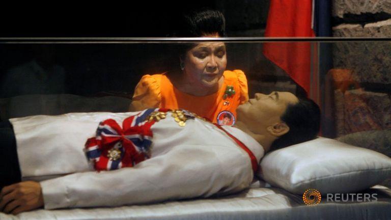 اميلدا ماركوس زوجة الدكتاتور السابق أمام التابوت الزجاجي المعروض فيه جثمانه