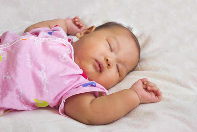 Asian baby sleeping on bed.