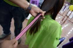 A woman has her hair cut during the first national Hair Donation Day, to donate it to a hospital for children with cancer, in Caracas on August 25, 2013. AFP PHOTO/Leo RAMIREZ        (Photo credit should read LEO RAMIREZ/AFP/Getty Images)